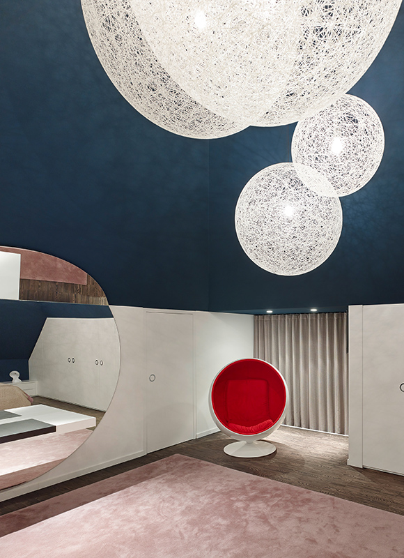 Master bedroom features a space age look, with floating light spheres in white above red-cushioned egg chair. Dark hardwood flooring contrasts with white walls and dark blue upper layer.