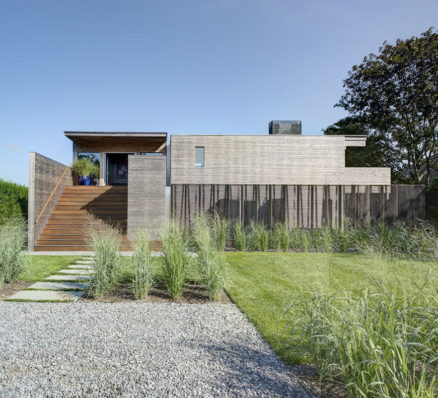 The home as seen approaching from the front. Stone path leads toward grand warm toned staircase between dividing walls of grey wood. The entire structure is minimal and angular, a flat presence hiding the complexity and ingenuity from this angle.