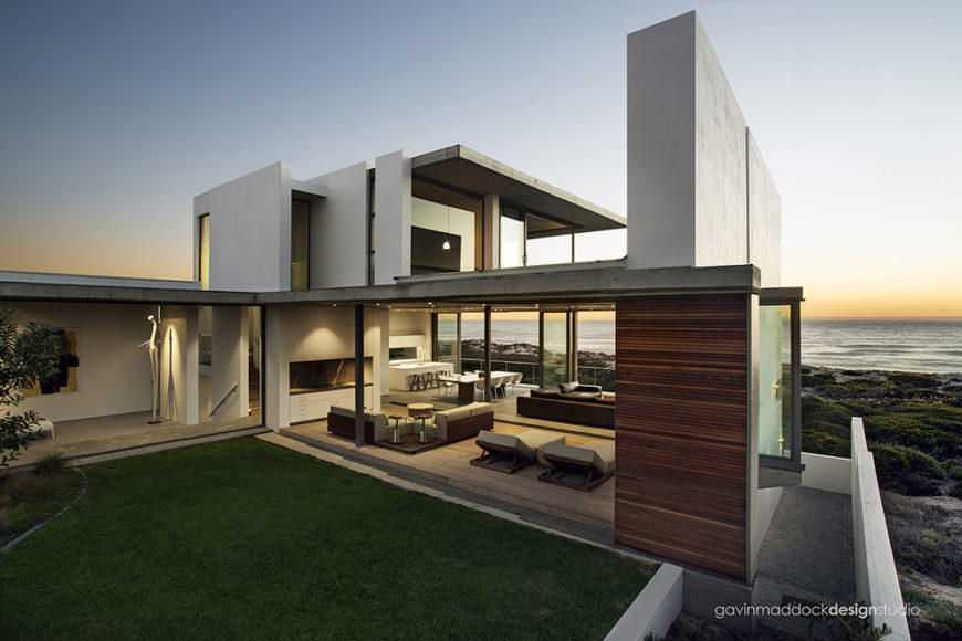 Wide view of the entire structure from oceanside, revealing the ambiguous line between indoor and outdoor spaces. Concrete slabs mix with natural wood paneling throughout the structure for unobtrusive, minimalist yet striking design.