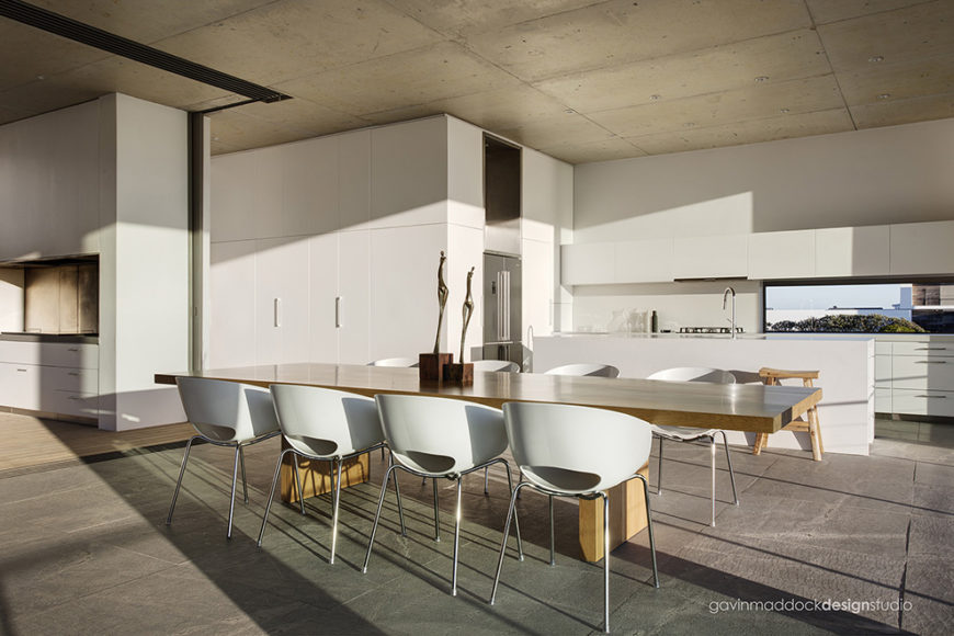 Turning toward the kitchen, we see a thoroughly smooth and minimalist white surface dominating the space. Large island, floor to ceiling cabinetry, and hallway walls all match in the bright tone, in contrast with the neutral greys of the rest of the open area.