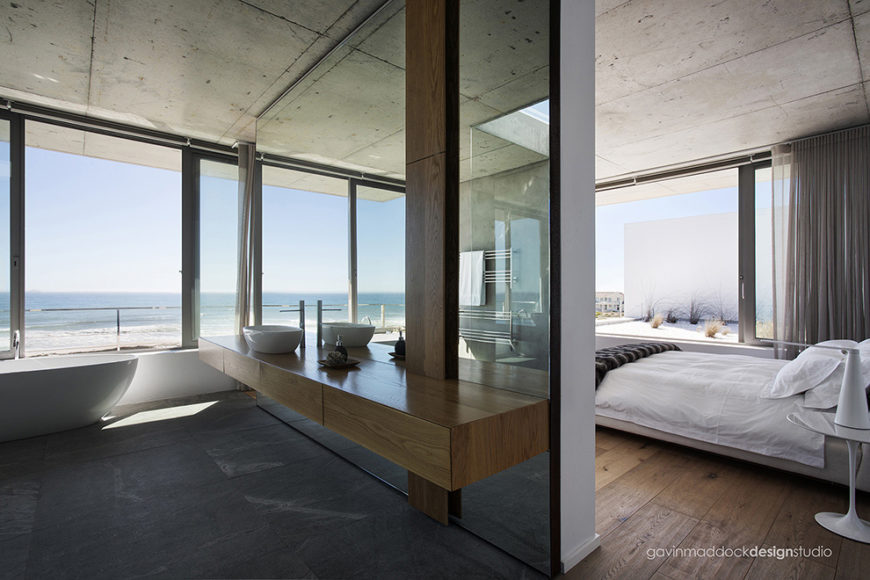 Master bedroom suite effortlessly combines bath and sleeping areas, with mirrors and floor to ceiling glass all around. Flooring defines the spaces, with stone in bathroom and hardwood in bedroom.