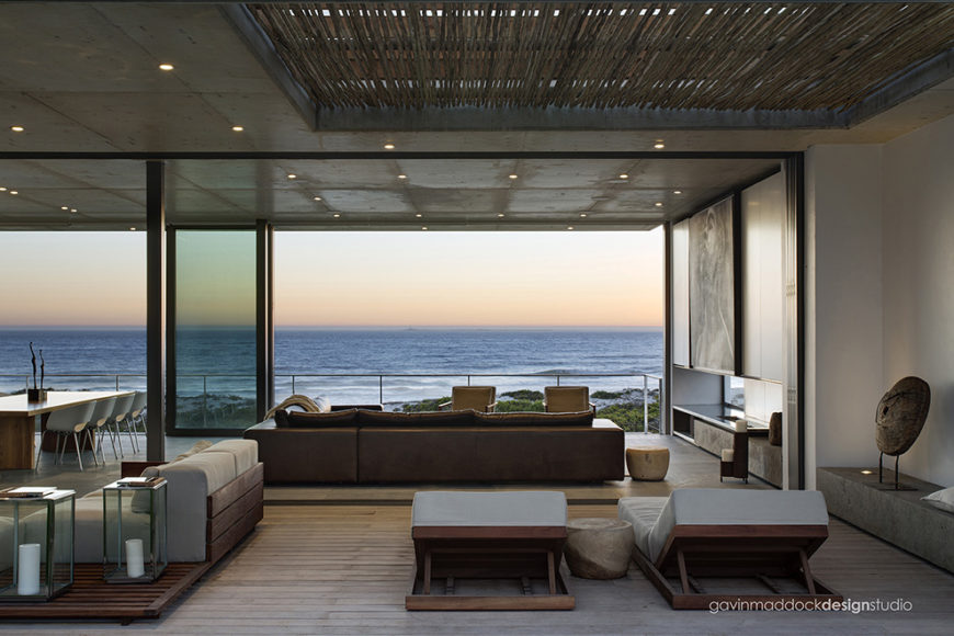 Central open living room seamlessly joins the patio space with sliding glass panels. Hardwood flooring continues through both areas, with leather sectional inside and wood frame lounge seating outside.