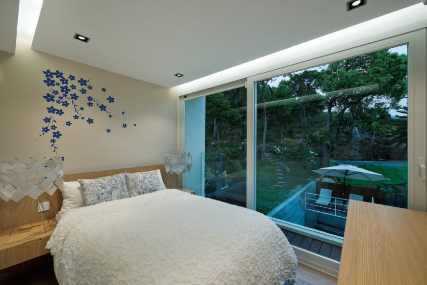 Second floor bedroom features light natural wood shelving built into bed frame, embedded ceiling lighting, and immense sliding glass panel opening to balcony.