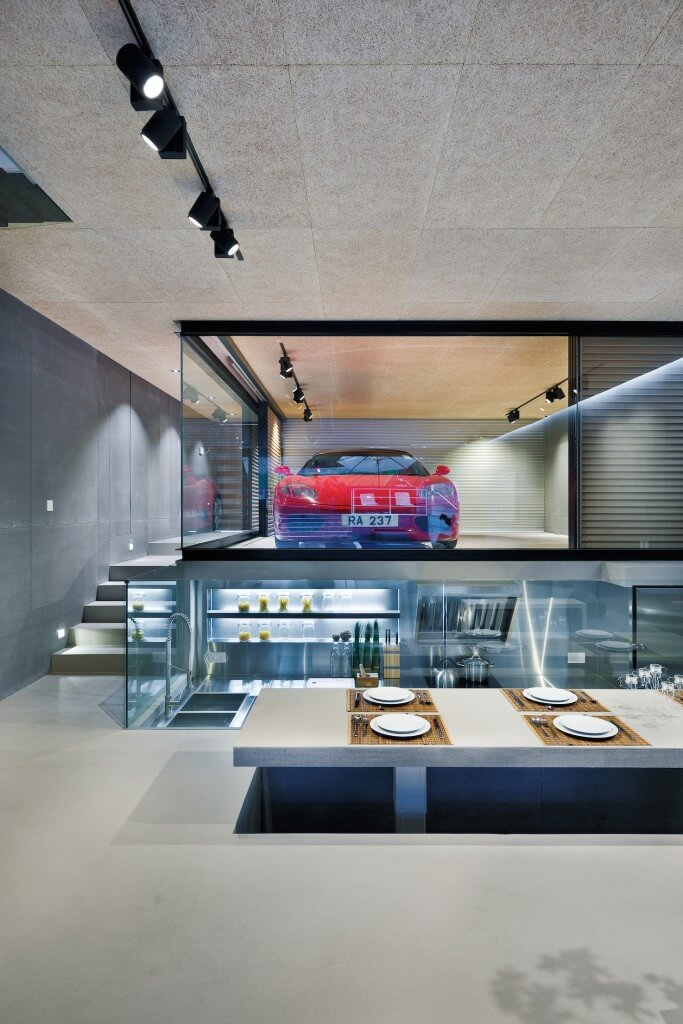 Glass wrapped garage sits within interior space, making for striking, unique display of the owner's Ferrari. Below this sits the kitchen, carved into the floor space.