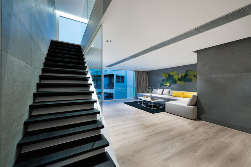 At the top of the first set of stairs, we have the second floor, awash in light natural wood flooring. Large grey sectional wraps around black rug and wire-frame cubic coffee tables.