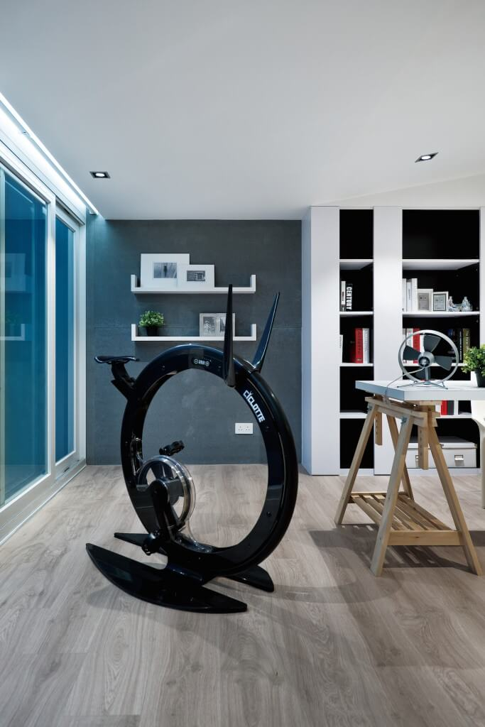 Close view of the ultra-modern stationary bike, standing near saw horse mounted desk and white wood shelving built into concrete exterior wall.