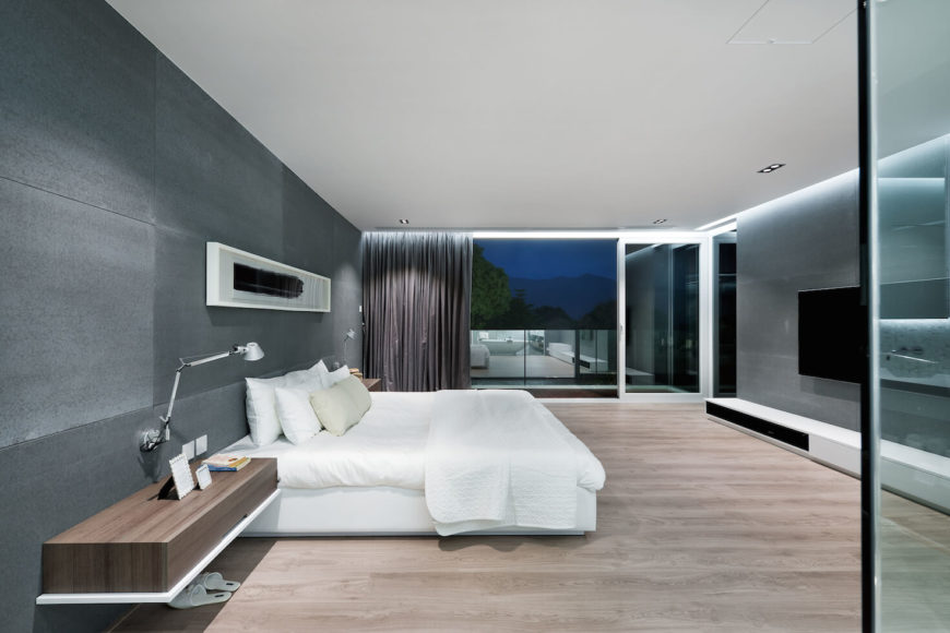 Master bedroom features expansive views over glass-walled balcony, plus wall-mounted wood shelves flanking the white bed.