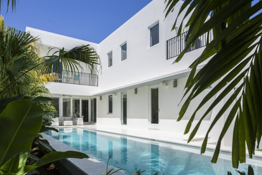 Lido pool runs the length of the rear facade, with white patio surrounding and tropical garden bordering outer edge.