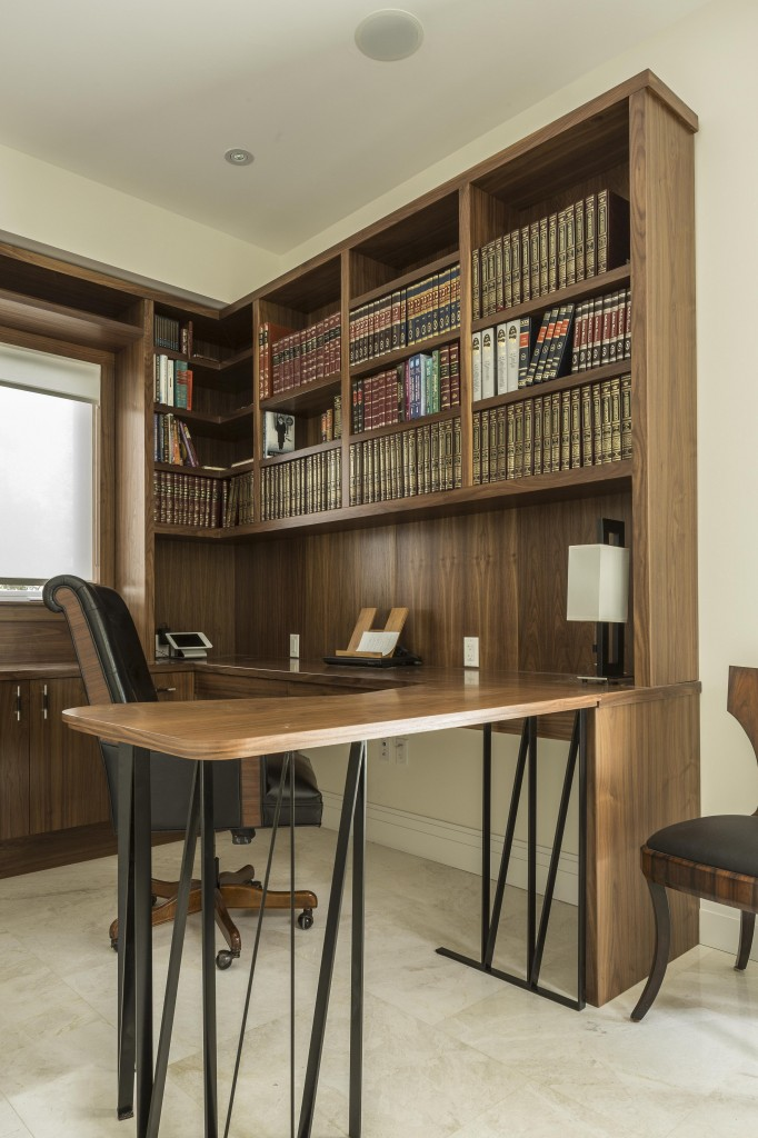 Office features more of the rich wood paneling, extending into wall structure, cabinetry, and this large wraparound desk with extensive bookshelves overhead.