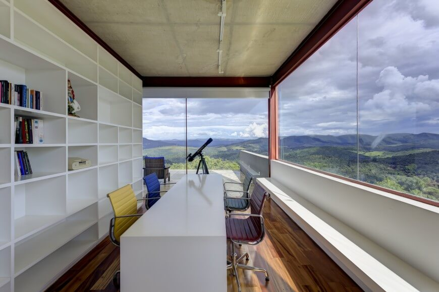 Library includes this semi-private office space, with lengthy white desk matching the kitchen decor, paired with a rainbow of wheeled chairs. Single bench runs length of the exterior wall, beneath windows with spectacular, expansive view.