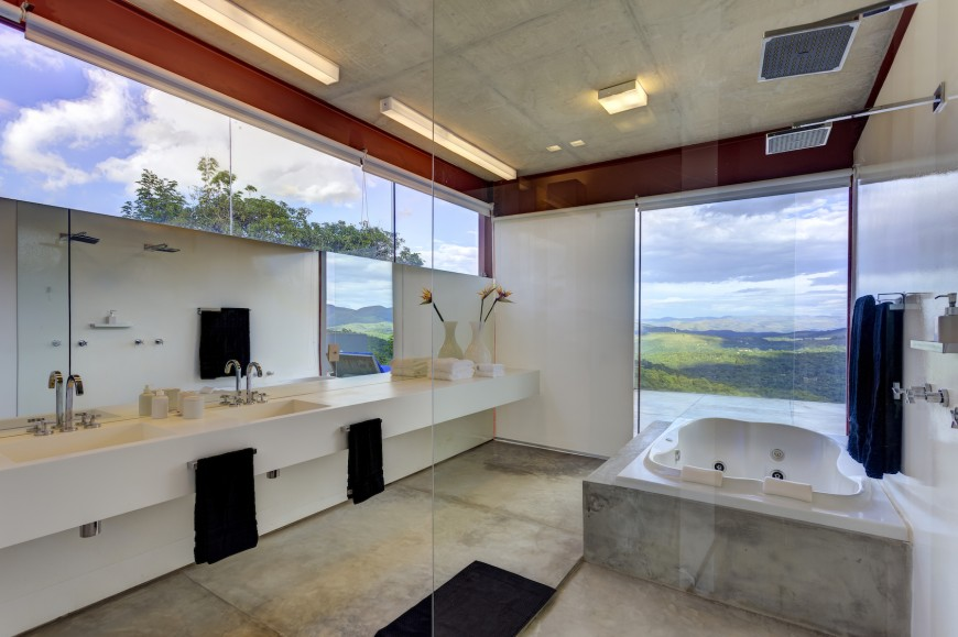 Master bath reiterates the minimalist, white theme with floating countertop backed by wall-length mirror, seamless glass shower, and large jacuzzi tub next to balcony access.