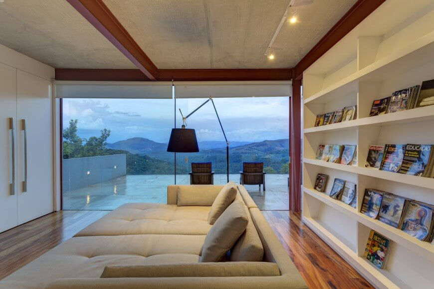 The upper level library features this immense low-profile sofa over natural hardwood flooring, with ceiling height bookshelf at right and massive balcony seen through external glass.
