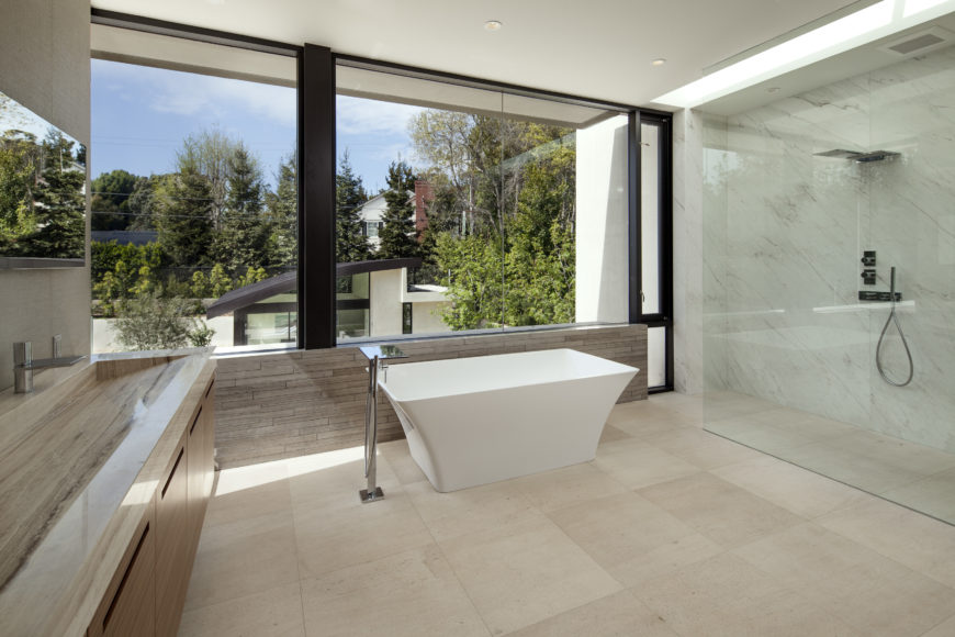 Master bath contains a lengthy marble trough-style sink, white pedestal tub basking in natural light, and massive walk-in glass shower on right.
