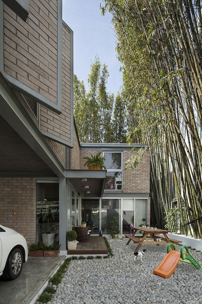 Patio space shares a covered, wood-floor area with this flattened rock garden next to the bamboo perimeter. Car port integrates with home structure at left, and numerous windows overlook the space.