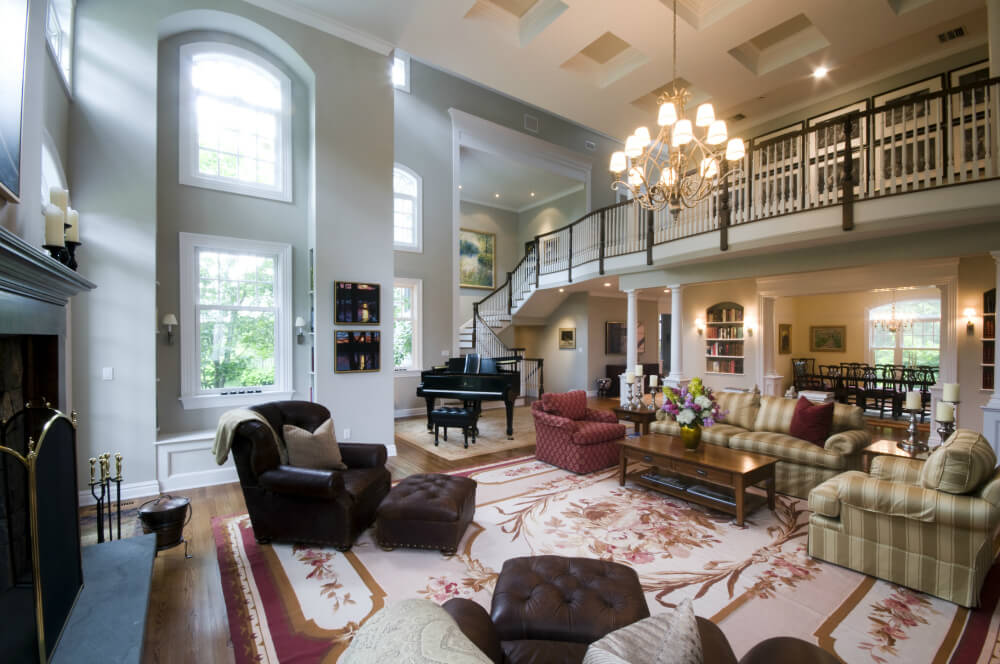 2 Story Great Room Decorating Ideas Part - 28: Massive Two Story Living Room Centered Around Red Floral Area Rug,  Featuring Dark Leather Chairs