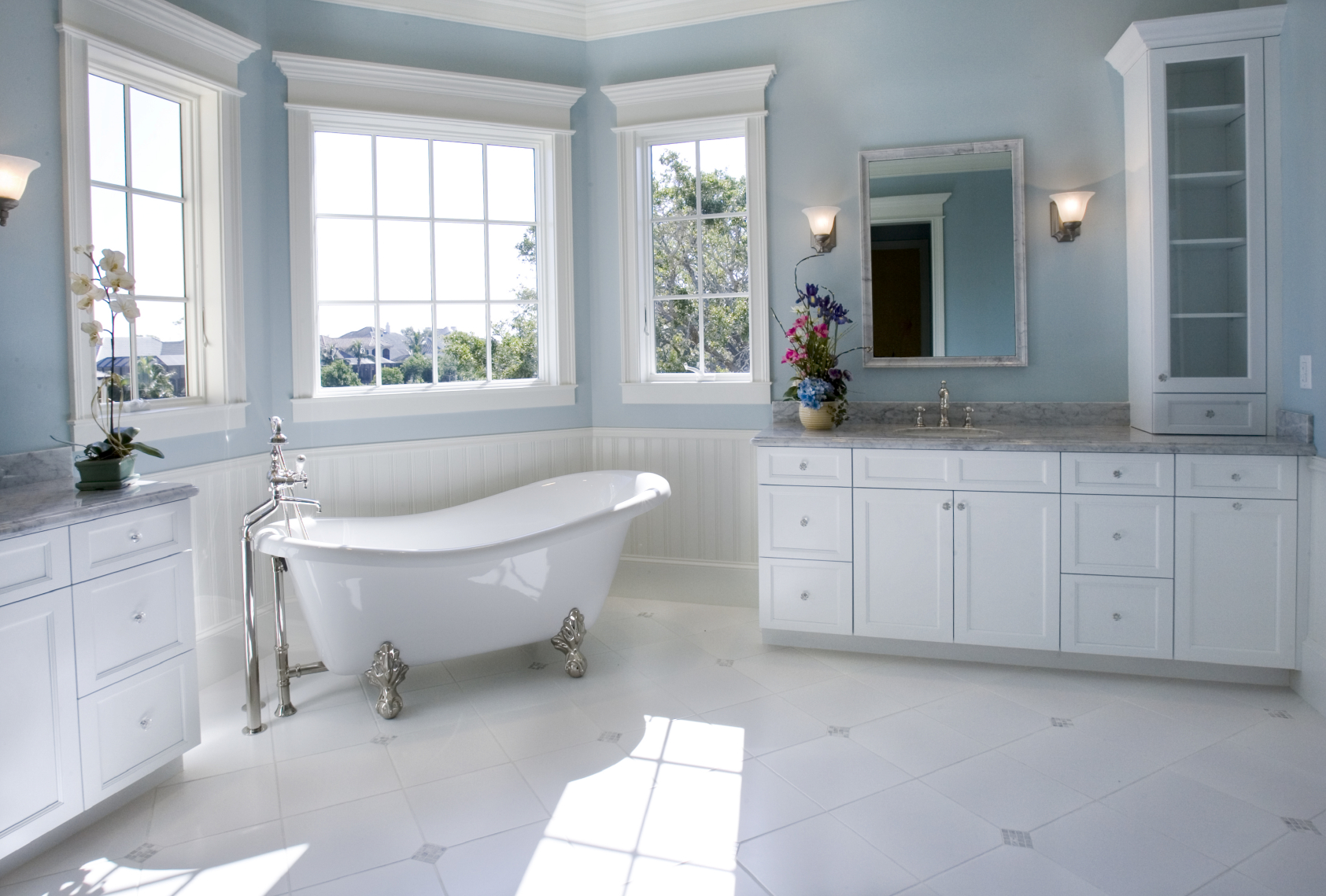 float above the white cabinetry and marble flooring in this bathroom