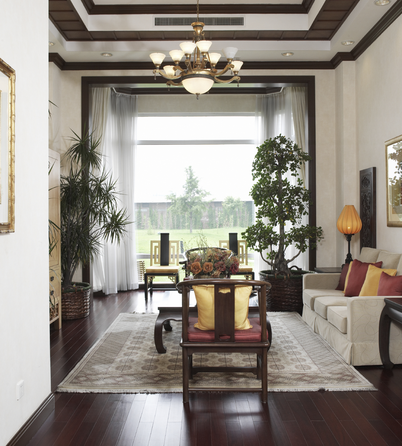 Rich red in the hardwood floor is brought out in the red chair cushions and red throw pillows. Just visible is a light wood entertainment center. Tray ceiling is white with brown crown molding.