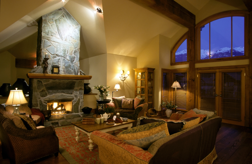 Cozy Rustic Styled Living Room Pairs Natural Wood Throughout With Free Standing Stone Fireplace