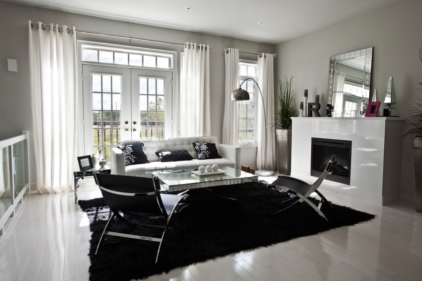 Stark Black And White Contrasts In This Modern Living Room With Stained Hardwood Flooring