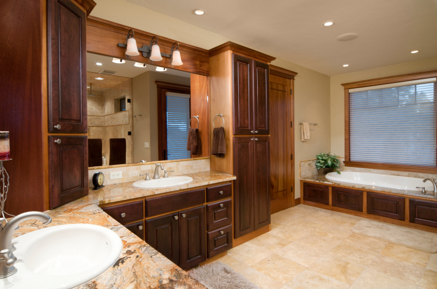 another wide bathroom featuring immense dark natural wood vanity cabinetry featuring swirled marble countertops and