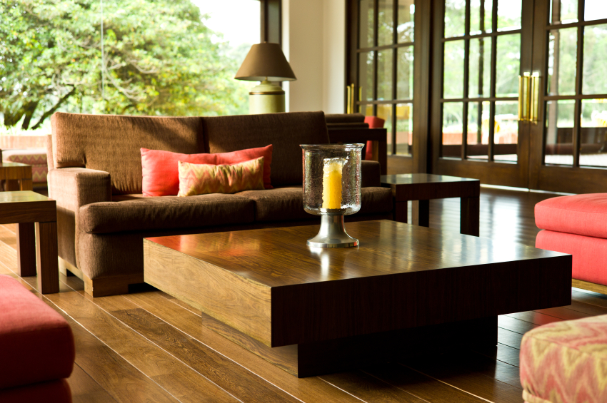 The wooden coffee table matches the hardwood floors so perfectly it appears to be an extension of them. Brown seating is matched with bright salmon pink and yellow.