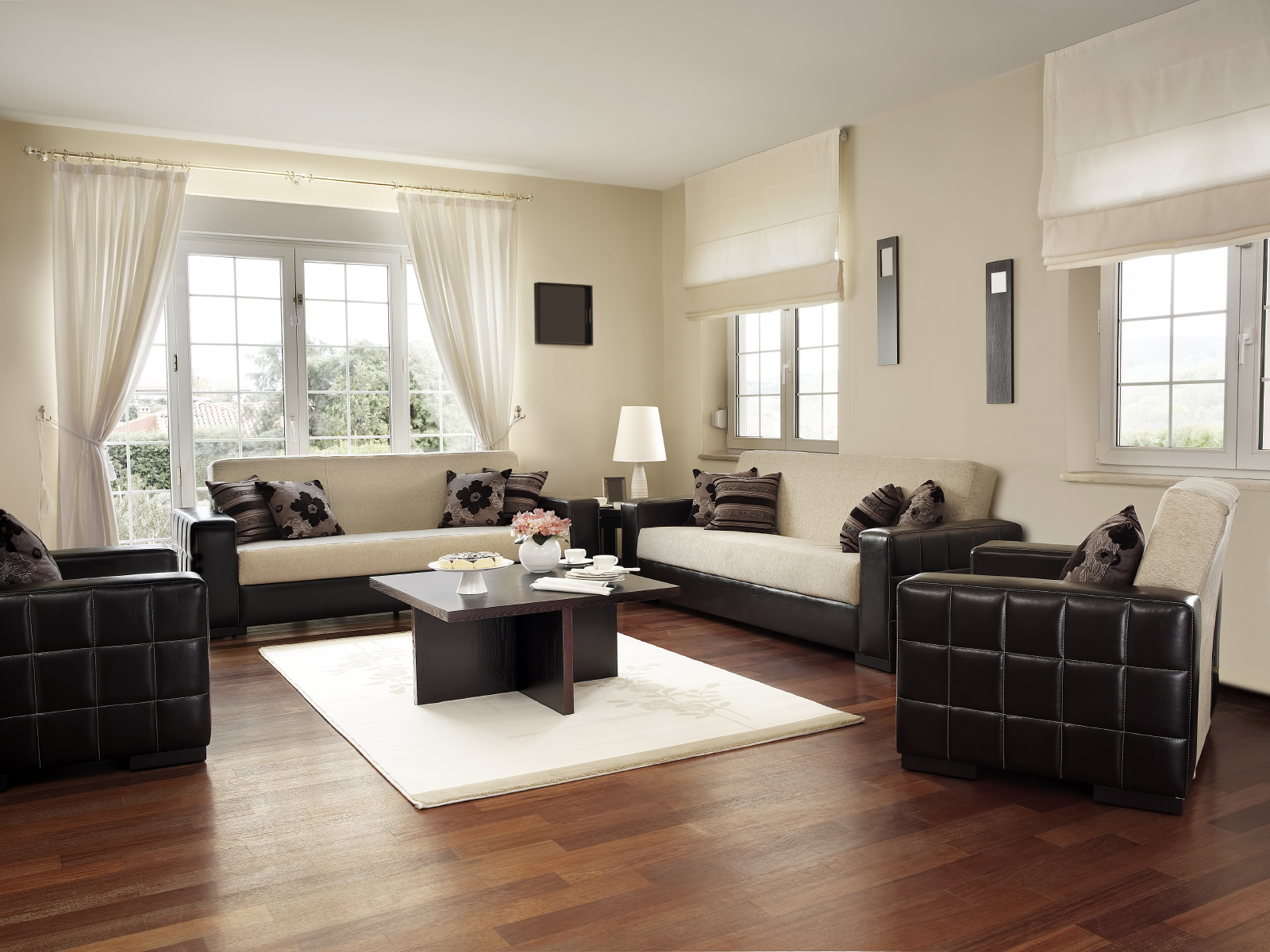 Couch and chair set with white single-piece cushions and black quilted arms. Roman shades on the two right windows. The couch is several feet in front of the glass doors, allowing for all the room's space to be utilized.