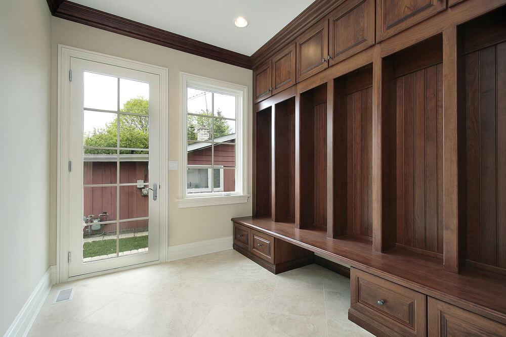 Side entrance mudroom with enormous dark wood bench and storage. Beige ...