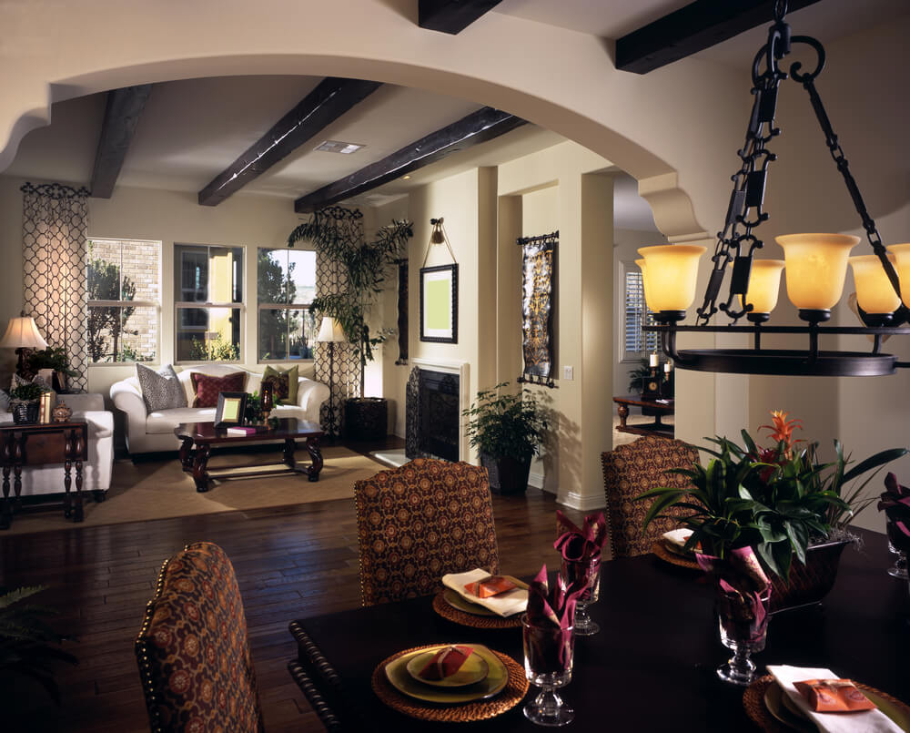 This small living room is overlooked by the dining room. Reds from the dark wood floor are picked up in the accent pillow, coffee table and side table. The ceiling has exposed wood beams.
