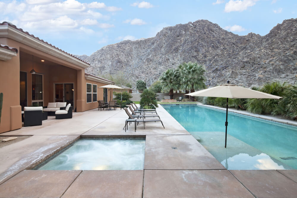 Here's another desert home with a backyard that is entirely made up of a huge patio, long pool and hot tub. The perimeter is desert bushes which affords the space privacy.
