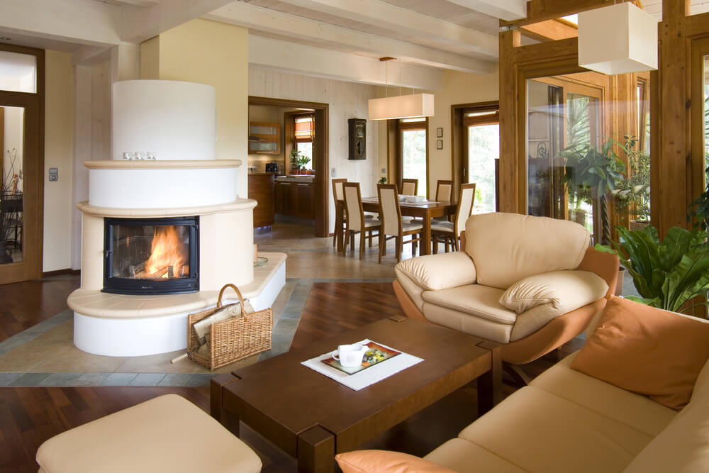 The enclosed fireplace is visible from both sides of the room, which leads into a small dining area. Natural hardwood floors give way to tile around the fireplace and dining area in the same way.