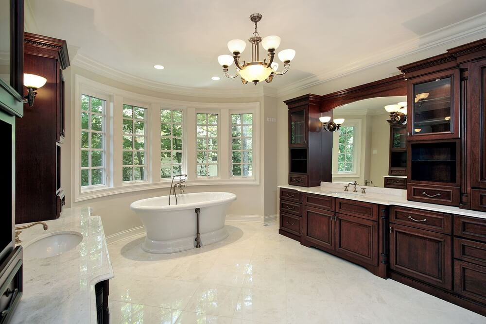 This white marble bathroom holds a pair of immense dark wood vanities, with array of cabinetry surrounding mirrors over marble countertops. White pedestal tub stands at center before curved windows.