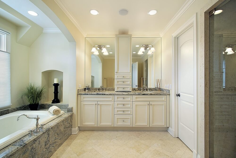 soft beige tones warm this bathroom featuring a dual vanity with countertop cabinet bisecting a