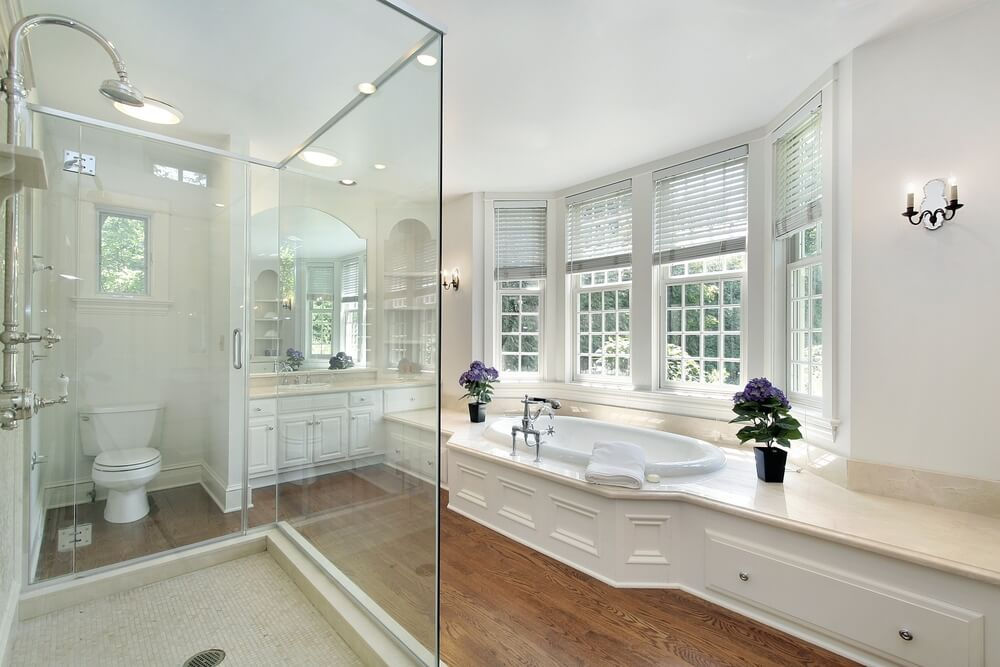 spacious contemporary white luxury bathroom with tub by bay window and