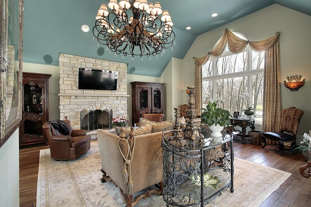 The stone fireplace melds into a media center, with the home speaker system hidden on the blue ceiling. The expansive window on the far wall is flanked by two hairs and an antique table.