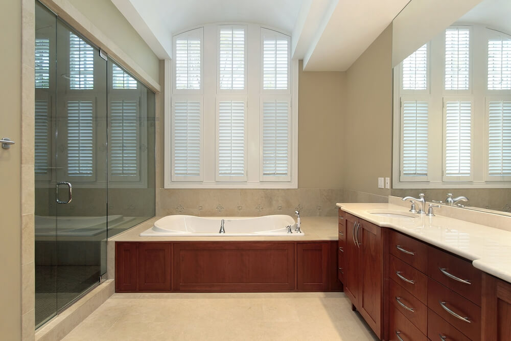 Intimate beige toned bathroom featuring smooth featured warm wood cabinetry and bath surround, light marble countertop, and tile flooring with glass entry shower at left.