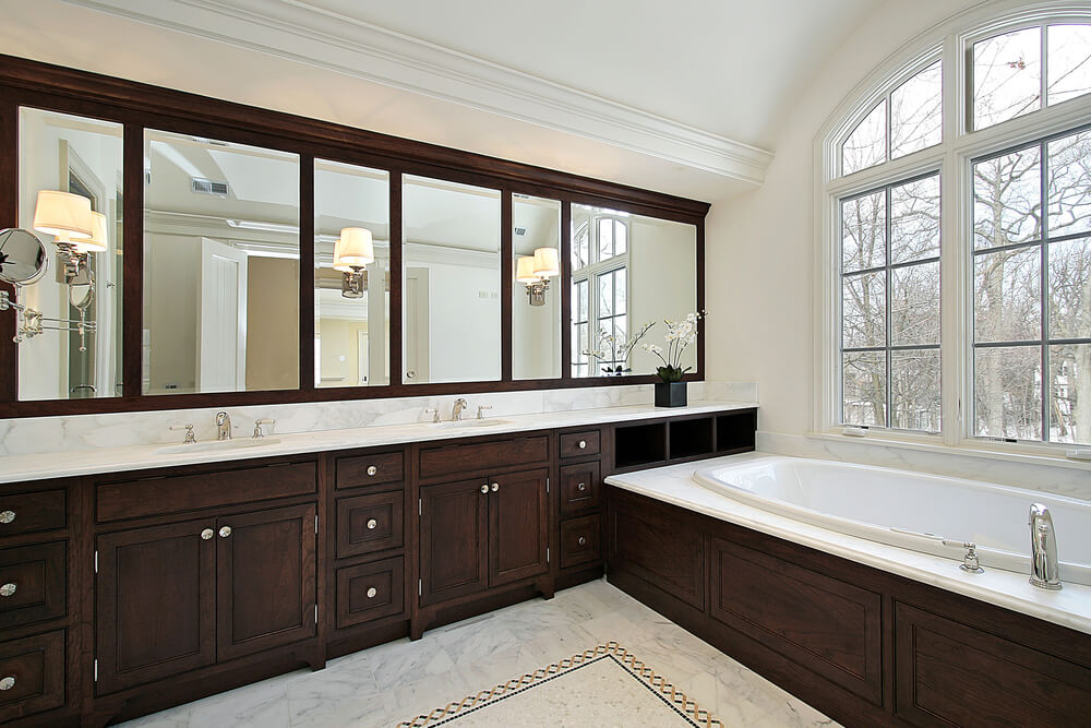 White bathroom with dark wood vanity running length of the room, with matching bath surround and mirror frames. Marble flooring is matched on countertops and bath surround.