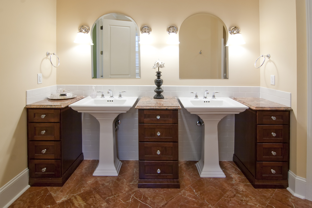Bathroom in light yellow tones over brown marble flooring features a pair of pedestal sinks standing between a trio of dark wood vanities with marble countertops.