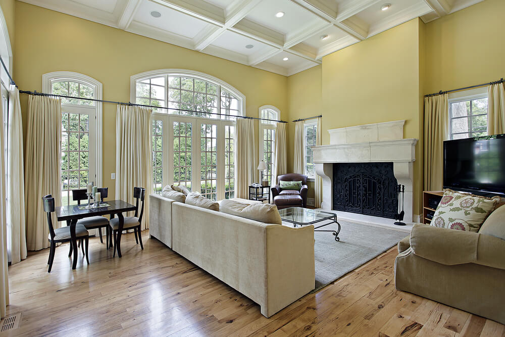 Coffered ceiling above sunny yellow walls and arched windows. A small table and chairs behind the couch, which sits in front of a large masonry fireplace.