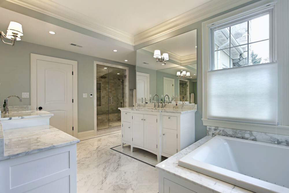 lavish white marble bathroom sprawls with dual vanities facing over the central space soaking tub