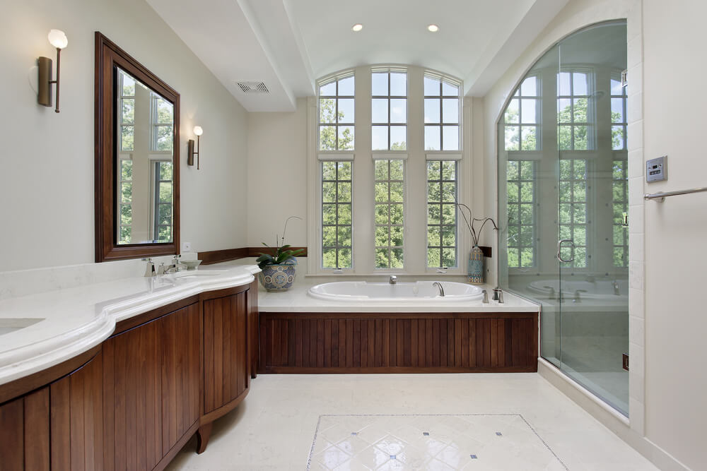 This arched ceiling bathroom in white features rich dark wood cabinetry and bathtub surround over white patterned tile flooring. Glass entry shower stands across from marble topped vanity.