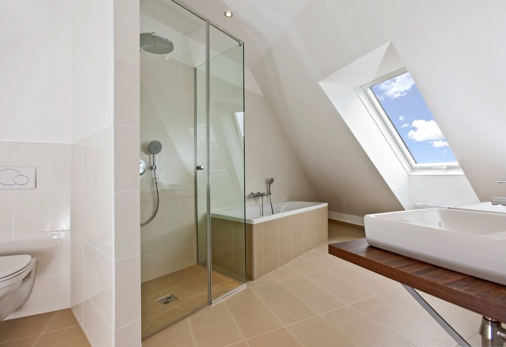angular modern bathroom naturally lit via skylight features large format beige tile throughout with
