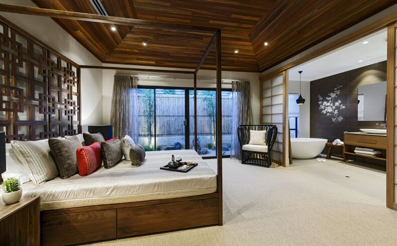 Vaulted timber ceiling soars over master bedroom suite, featuring natural wood canopy bed across from shoji screened private bathroom with white pedestal tub and black vanity wall with floral art print.