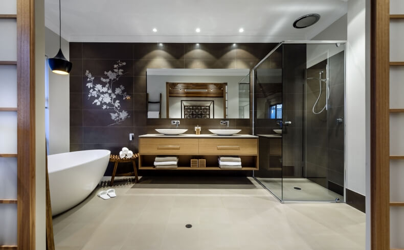 View into the master bath reveals natural wood vanity with twin vessel sinks, pure glass walk in shower, and detailed view of the delicate floral print on dark mirror mounted wall.