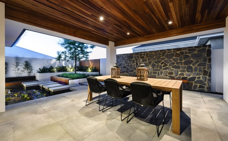 """Patio space heightens the Zen garden feel, with """"floating"""" stone platforms surrounding a small pool, white concrete walls supporting corner manicured garden, and more of the ceiling timber overhead protected dining space."""