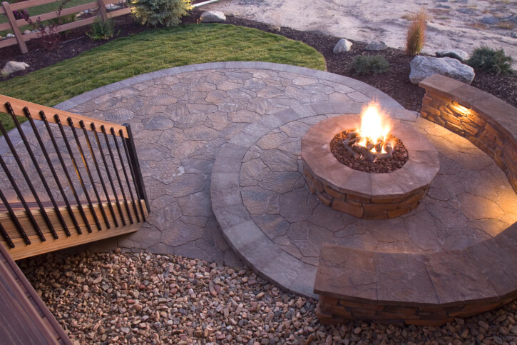Fire pit in the center of a radial flagstone patio.