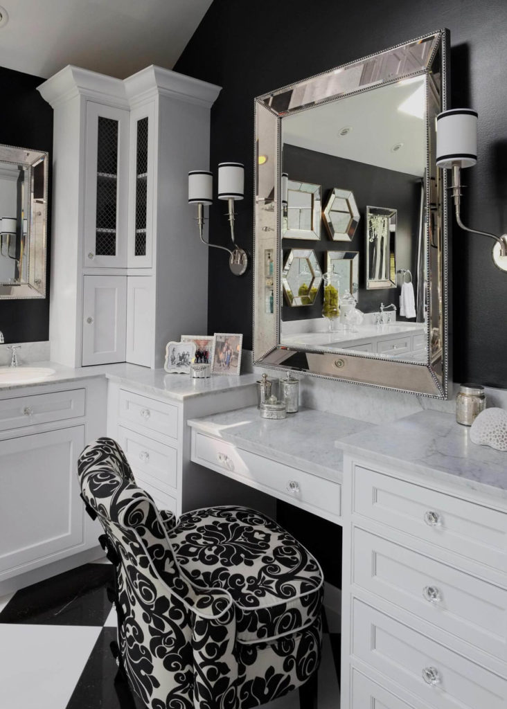 The vanity chair mixes the recurring black and white theme into a playful design. Mirror and cabinet hardware boast a detailed, crystalline look, surrounding the solid marble countertops.