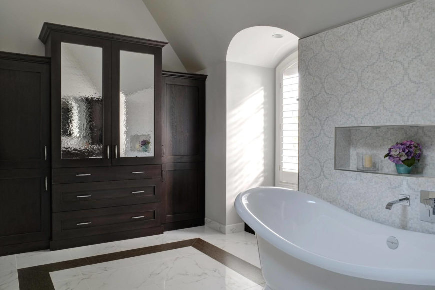 Where the original tub was placed, we now have an immense armoire with watery glass door panels. The entire wall is occupied by the lush, dark cabinetry for ample storage.