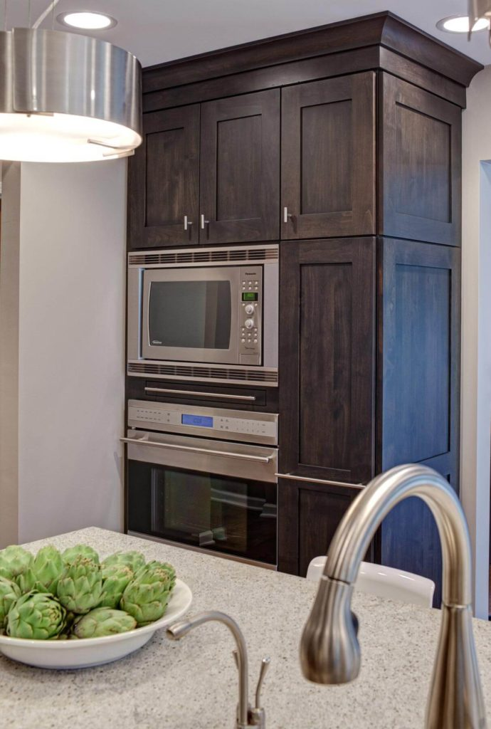 The oven cabinetry seen here seamlessly integrates the microwave, warming shelf, and additional storage to the right, all in the chocolate toned wood.