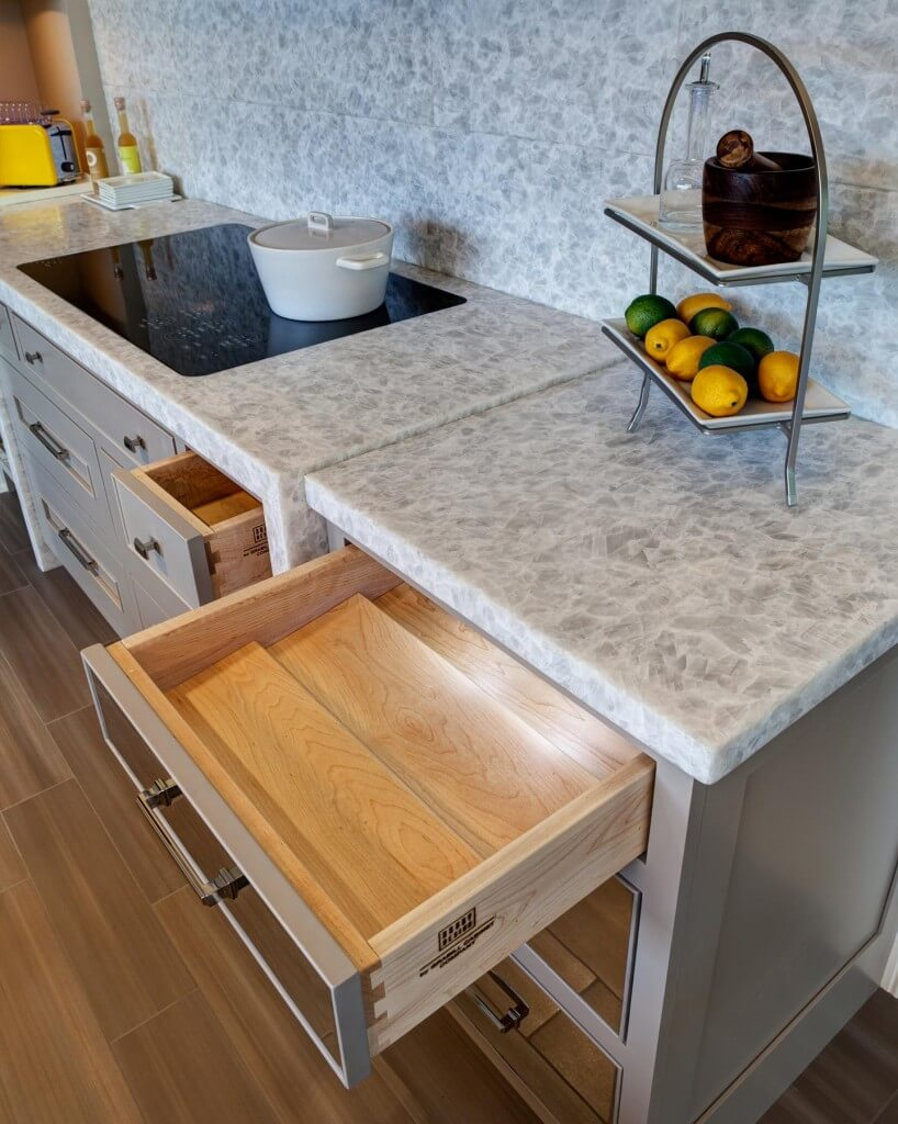 Close view of the quartzite countertops, with matching material set in tiled backsplash above.