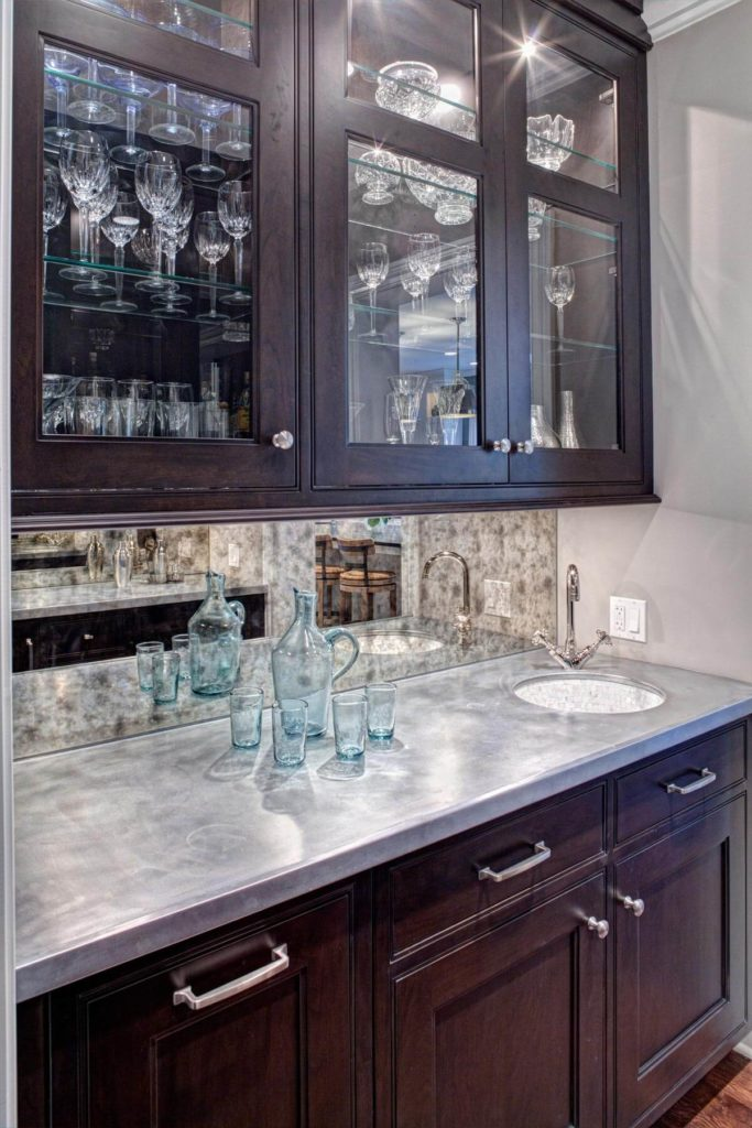 Dark stained wood cabinetry surrounds this metal countertop with mirrored backsplash in a separate bar space. Upper cupboards feature interior lighting behind glass panel doors.